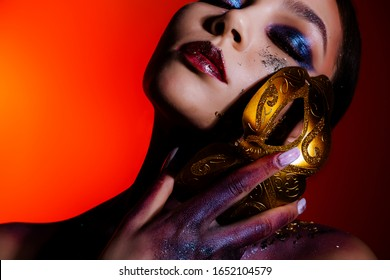 Fashion portrait of a young woman with closed eyes and creative make-up, body art with a masquerade mask in her hands. Masquerade mask in female hands on an orange background. Masquerade, festival.