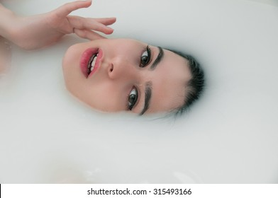 Fashion portrait of young woman floating in Spa filled with milk