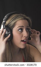 fashion portrait of young woman  listening to music over black background