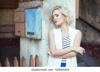 Fashion portrait of young woman outdoor near vintage post letter box and obsolete wall. Beauty female portrait. Charming Lady.