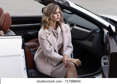 Fashion portrait of young woman in pink coat and dress outdoor in cabriolet car