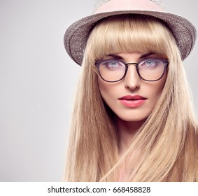 Fashion Portrait Young woman in Stylish Glasses. Sexy Blond Girl. Sensual Beauty Model, Shiny Hairstyle. Blue eyes. Glamour Trendy Hat. Luxury fashionable Summer Outfit.