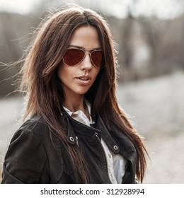 Fashion portrait of young woman in sunglasses - close up