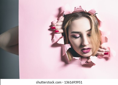 fashion portrait of a young woman tearing a hole in pink cardboard paper, face of a girl with makeup, creative concept freedom of beauty, fashion, cosmetics, youth lifestyle