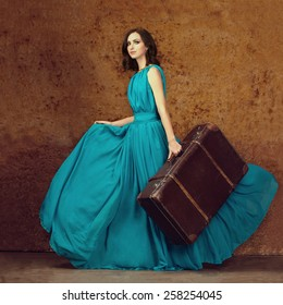 Fashion portrait of young woman walking with old suitcase. Travel concept