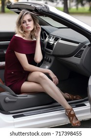 Fashion portrait of young woman in wine color dress outdoor in cabriolet car