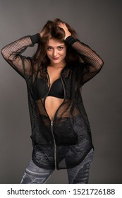 Fashion portraiture of a sexy young Caucasian woman in leggings and black bra  with fishnet hoodie top isolated over grey background. Studio fashion sexy lifestyle concept.