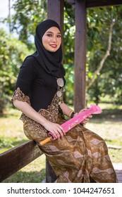 Fashion portraiture of young beautiful malay woman wearing modern kebaya holding traditional chinese pink umbrella.