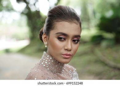 Fashion portraiture of young beautiful woman wearing beautiful dress. Image contain certain grain or noise and soft focus.