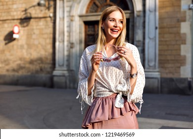 Fashion positive portrait of elegant woman posing at old European city, wearing luxury silk skirt and blouse, holding sunglasses, natural make up and long blonde hairs, traveling mood.