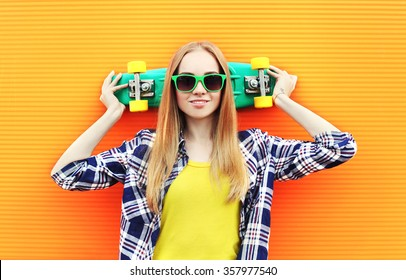 Fashion pretty blonde girl wearing a sunglasses with skateboard having fun over colorful background