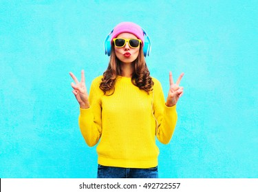 Fashion pretty cool girl in headphones listening to music wearing colorful pink hat yellow sunglasses and sweater over blue background