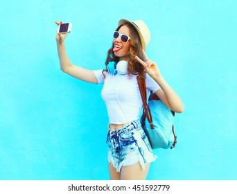 Fashion pretty cool girl makes self portrait on smartphone over blue background