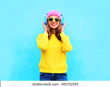Fashion pretty cool smiling girl listening to music in headphones wearing colorful pink hat, yellow sunglasses and sweater over blue background