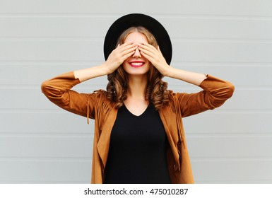 Fashion pretty cool young woman closes eyes cute smiling wearing a vintage elegant hat brown jacket playing having fun over grey background