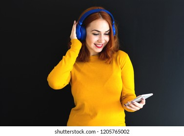 Fashion pretty girl listening to music in headphones with smartphone wearing a colorful yellow sweater over black background. Music, lifestyle concept.