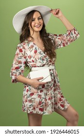 fashion pretty girl in summer dress with a white hat a bag. she is posing and smiling in camera