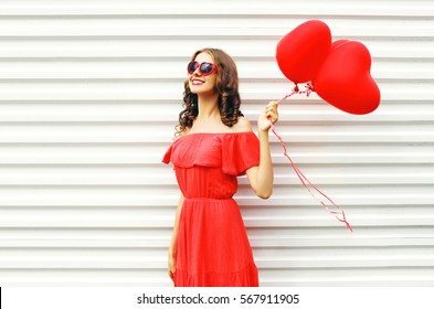 Fashion pretty happy smiling woman in red dress and sunglasses with air balloons heart shape looking up over white background