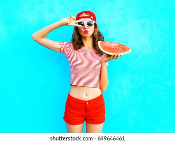 Fashion pretty slim woman is holding a slice of watermelon over a colorful blue background wearing a red baseball cap