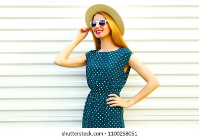 Fashion pretty smiling woman in a dress, straw round hat on white background