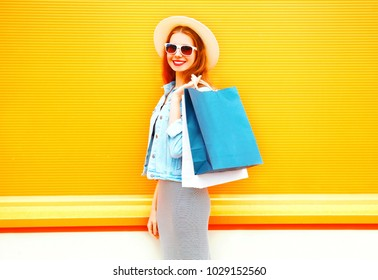 Fashion pretty smiling woman with shopping bags, straw hat on a orange background