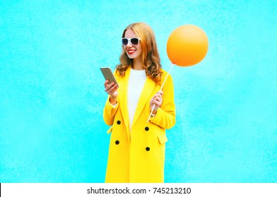 Fashion pretty smiling woman using smartphone holds an air balloon on a colorful blue background