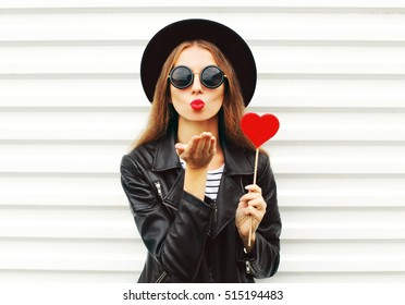 Fashion pretty sweet young woman with red lips sends air kiss with lollipop heart wearing black hat leather jacket over white background