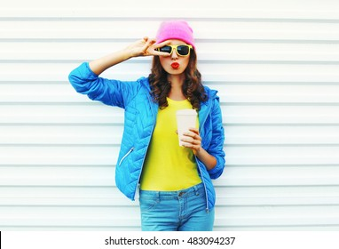 Fashion pretty woman with coffee cup in colorful clothes over white background wearing a pink hat yellow sunglasses blue jacket