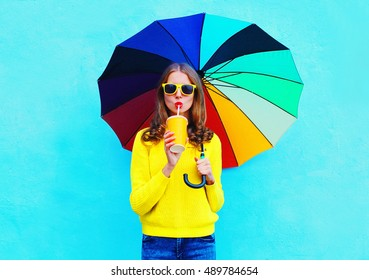 Fashion pretty woman with fresh fruit juice cup and colorful umbrella in autumn day over blue background wearing a yellow knitted sweater