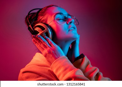Fashion pretty woman with headphones listening to music over red neon background at studio.
