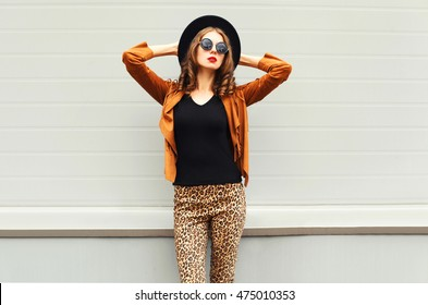 Fashion pretty woman model wearing a black hat, sunglasses and jacket over urban grey background
