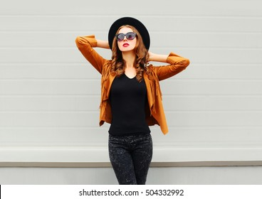 Fashion pretty woman model wearing a black hat, sunglasses, jacket posing over grey background