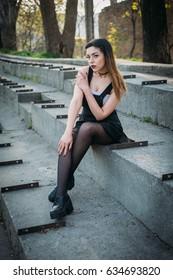 Fashion pretty woman model wearing a balck sarafan. Sitting on the stairs of abandoned stadium
