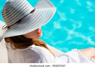 Fashion Pretty woman on summer vacation relaxing at luxury hotel resort spa poolside. Young  fashionable lady wearing sun hat and white kaftan.