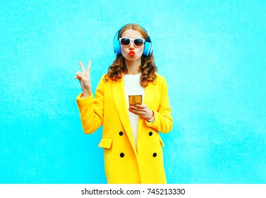 Fashion pretty woman with smartphone listens to music in headphones on a colorful blue background