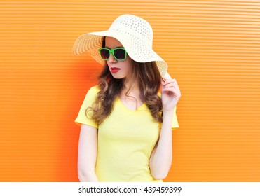Fashion pretty woman in sunglasses and straw hat over colorful background