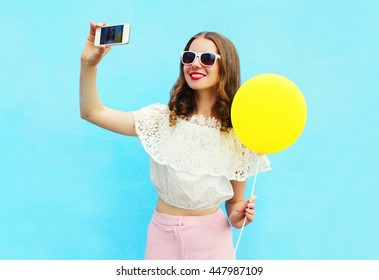 Fashion pretty woman taking picture makes self portrait on smartphone with yellow air balloon over colorful blue background