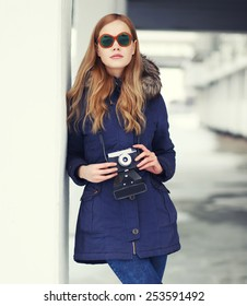 Fashion pretty woman in unusual sunglasses with vintage retro camera outdoors