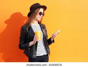 Fashion pretty woman using smartphone in rock black style over colorful orange background