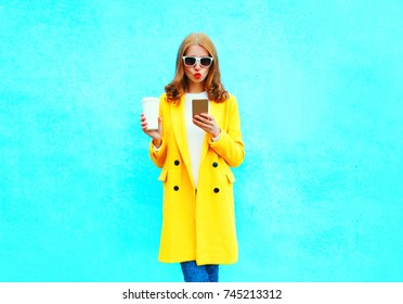 Fashion pretty woman using smartphone with cup of coffee on a colorful blue background