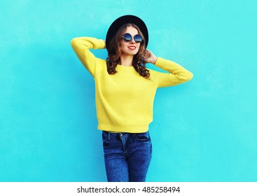 Fashion pretty woman wearing black hat and yellow knitted sweater over colorful blue background