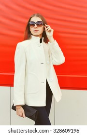 Fashion pretty woman wearing a white coat jacket with clutch bag over red background
