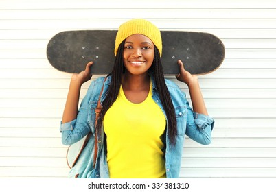 Fashion pretty young smiling african woman with skateboard in colorful clothes over white background