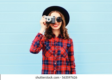 Fashion pretty young smiling woman holds retro camera wearing black hat, red checkered shirt over blue background