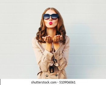 Fashion pretty young woman blowing red lips sends sweet kiss wearing a black sunglasses coat over grey background
