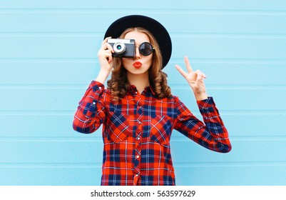Fashion pretty young woman blowing red lips with retro camera wearing a black hat, red checkered shirt over blue background
