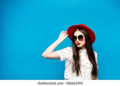 Fashion pretty young woman blowing red lip swearing a black hat sunglasses and red hat.