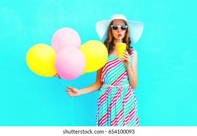Fashion pretty young woman drinks a fruit juice from cup with an air colorful balloons over a blue background