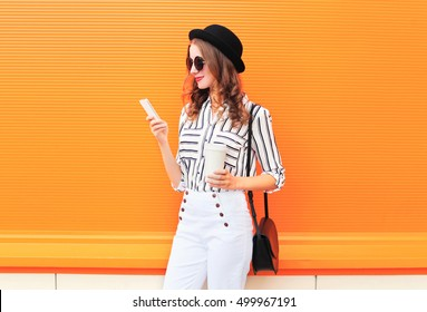 Fashion pretty young woman model using smartphone with coffee cup wearing black hat white pants over colorful orange background