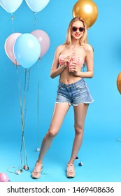 Fashion pretty young woman wearing a swimsuit, sunglasses,shorts drinks fruit juice from cup over blue background. full length photo.